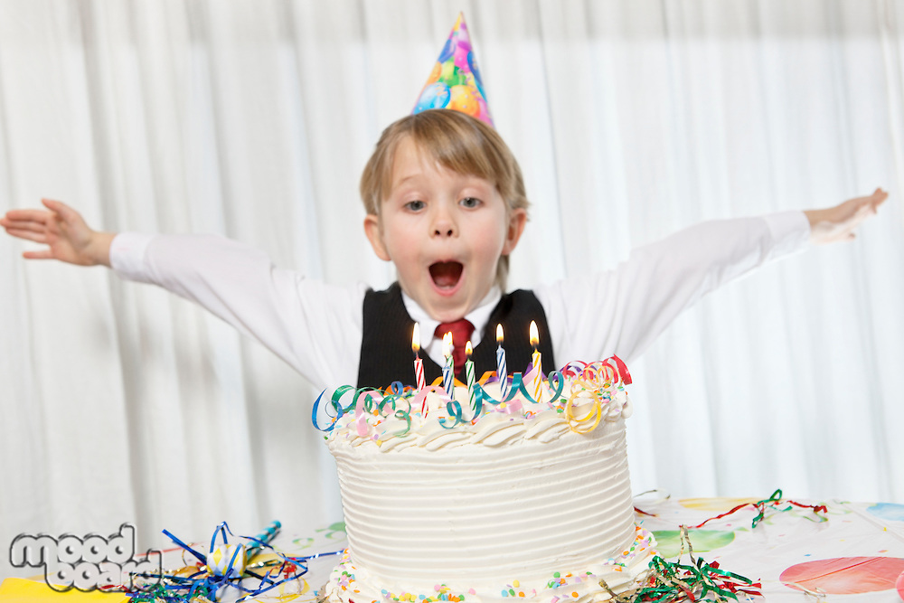 Young birthday wearing party hat with arms outstretched blowing candles on cake