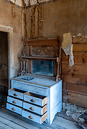 Empty abandoned dresser with mirror in Tom Miller house at Bodie State Historic Park. Remnants of wallpaper peel and hang rom the wall.