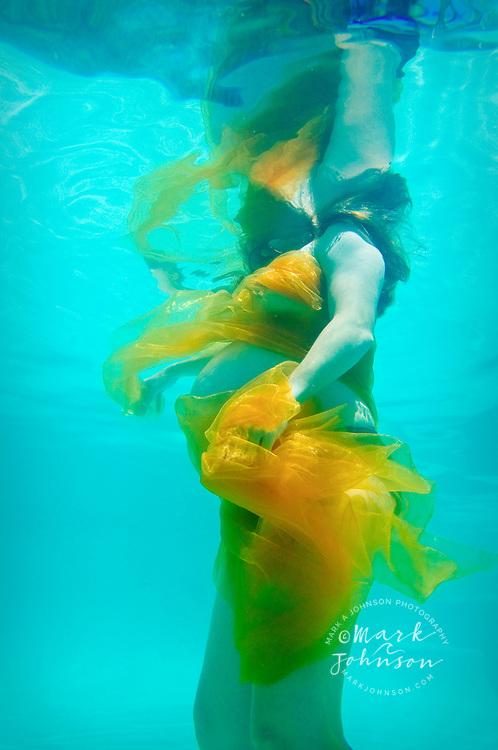 Pregnant woman underwater in pool