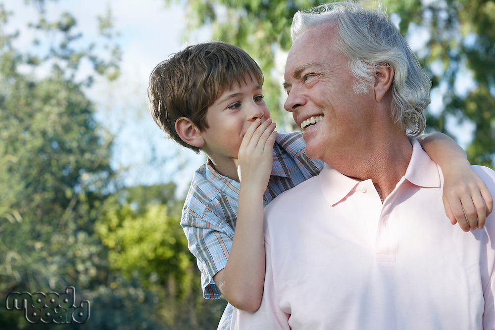 Grandfather with grandson (7-9) riding piggy back outdoors talking