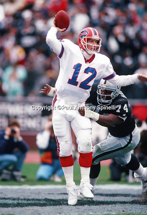 Buffalo Bills quarterback Jim Kelly (12) throws a pass while pressured by Los Angeles Raiders  defensive lineman Nolan Harrison (74) during the NFL football game against the Los Angeles Raiders on Dec. 8, 1991 in Los Angeles. The Bills won the game 30-27 in overtime. (©Paul Anthony Spinelli)