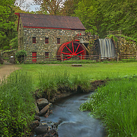 The Grist Mill in Sudbury Massachusetts photographed on a beautiful spring morning. It's always a good idea to hung around a bit especially when there are signs that the sky may be opening up. In this case I was occupied taken closer more intimate image of the Sudbury Grist Mill when the sky finally broke open and the scenery became alive. The warm morning sunlight painted the tree canopies in beautiful spring colors which stand in nice contrast with the darker foreground of the historic landmark. A long exposure setting conveys the flowing water of the brook in front of the view and across the waterfall at the Grist Mill.<br />