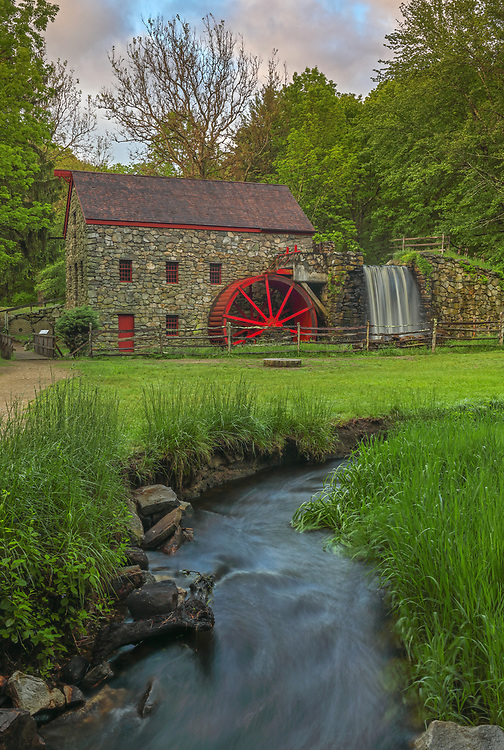 The Grist Mill in Sudbury Massachusetts photographed on a beautiful spring morning. It&rsquo;s always a good idea to hung around a bit especially when there are signs that the sky may be opening up. In this case I was occupied taken closer more intimate image of the Sudbury Grist Mill when the sky finally broke open and the scenery became alive. The warm morning sunlight painted the tree canopies in beautiful spring colors which stand in nice contrast with the darker foreground of the historic landmark. A long exposure setting conveys the flowing water of the brook in front of the view and across the waterfall at the Grist Mill.<br /> <br /> Wayside Inn Grist Mill photography pictures are available as museum quality photo, canvas, acrylic, wood or metal prints. Wall art prints may be framed and matted to the individual liking and interior design decoration needs:<br /> <br /> https://juergen-roth.pixels.com/featured/the-grist-mill-in-sudbury-juergen-roth.html<br /> <br /> Good light and happy photo making!<br /> <br /> My best,<br /> <br /> Juergen<br /> Licensing: http://www.rothgalleries.com<br /> Photo Prints: http://fineartamerica.com/profiles/juergen-roth.html<br /> Photo Blog: http://whereintheworldisjuergen.blogspot.com<br /> Instagram: https://www.instagram.com/rothgalleries<br /> Twitter: https://twitter.com/naturefineart<br /> Facebook: https://www.facebook.com/naturefineart