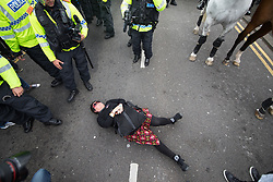 © Licensed to London News Pictures . 03/06/2017 . Liverpool , UK . A woman lies in the road and blocks the EDL march from progressing , outside Liverpool Lime Street Station . Hundreds of police manage a demonstration by the far-right street protest movement , the English Defence League ( EDL ) and an demonstration by opposing anti-fascists , including Unite Against Fascism ( UAF ) . Photo credit: Joel Goodman/LNP