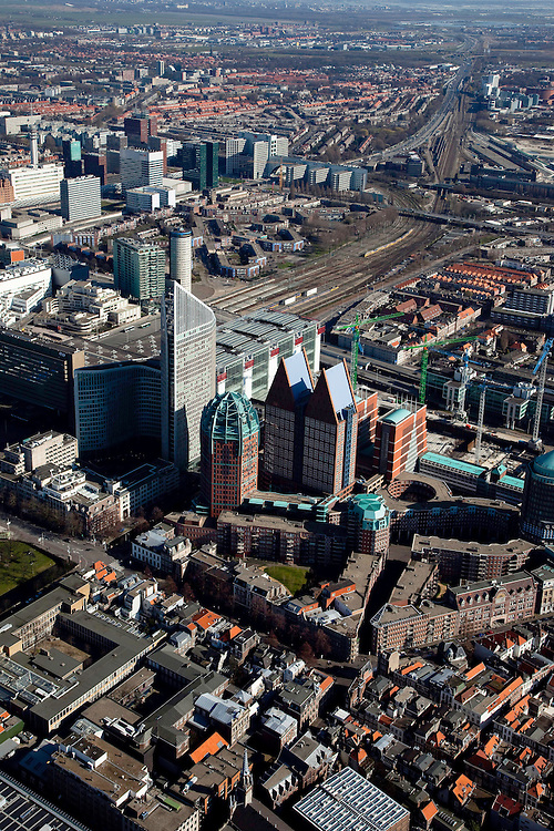 Nederland, Zuid-Holland, Den Haag, 20-03-2009; Hoogbouw van ministeries aan de Muzenstraat, rond het Clioplein. Links de Hoftoren (ministerie OCW) met ministerie van VROM er achter, deels verscholen. De rode bakstenen toren met groene bovenkant is de Zurichtoren (huisvest onder andere de OPTA en NMA), de dubbel toren met blauwe daken is Castalia, bijgenaamd de Haagse Tieten - ministerie VWS. De kranen staan aan de bouwput van de JuBi (Justitie en Binnenlandse zaken). Links Centraal Station met sporen, links hiervan kantoorgebouwen aan de Utrechtsebaan. View on The Hague.  High rise houses the Ministeries of Education. Next to the Central Station (l), the Ministry of Housing and of Education. The blue roofed twin buildings are called The Tits of The Hague, residence of the Ministry of Health. .Swart collectie, luchtfoto (toeslag); Swart Collection, aerial photo (additional fee required); .foto Siebe Swart / photo Siebe Swart