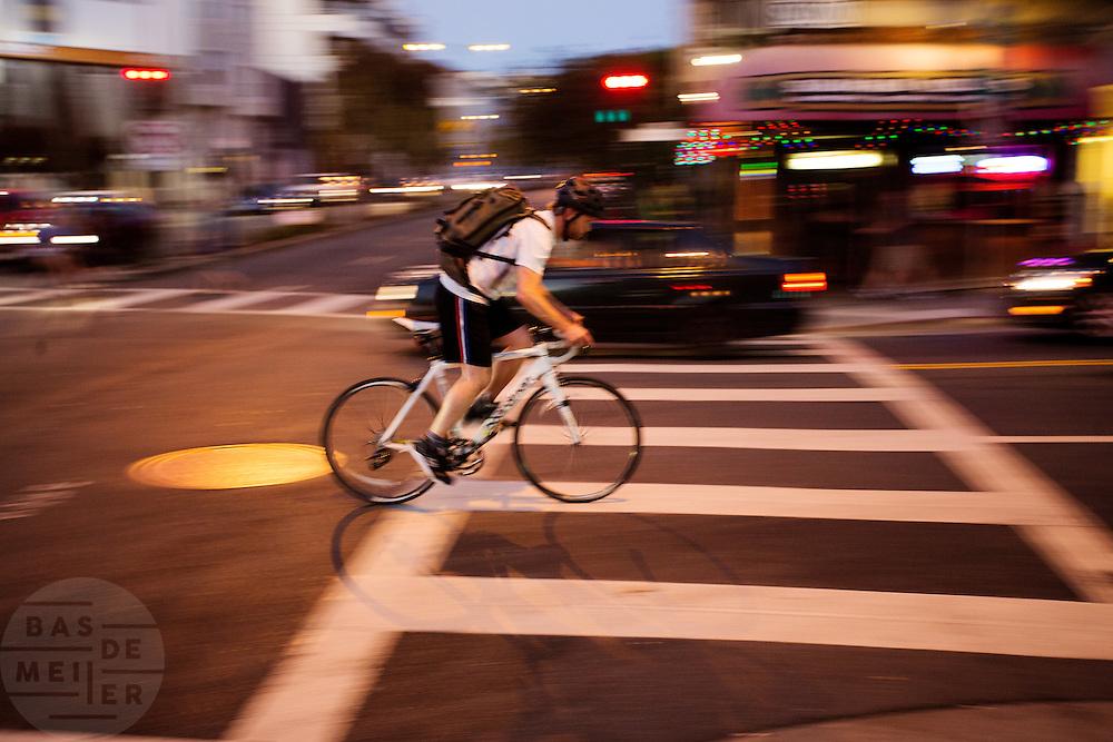 In San Francisco fietst een man &rsquo;s avonds op Polk Street. De Amerikaanse stad San Francisco aan de westkust is een van de grootste steden in Amerika en kenmerkt zich door de steile heuvels in de stad. Ondanks de heuvels wordt er steeds meer gefietst in de stad.<br /> <br /> Cyclists in San Francisco. The US city of San Francisco on the west coast is one of the largest cities in America and is characterized by the steep hills in the city. Despite the hills more and more people cycle.