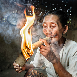 Woman smoking a big cigar made out of corn leaves and tobacco, Bagan, Myanmar, Asia