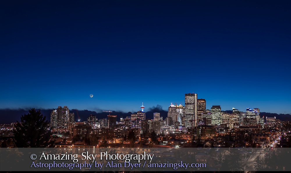 The waxing crescent Moon over the skyline of Calgary on January 18, 2018.  I shot this from Tom Campbell Park area looking southwest to the sunset twilight. <br /> <br /> This is a 2-segment panorama, each segment being a 7-image HDR stack, all blended with Adobe Camera Raw. Shot with the 50mm lens and Canon 6D MkII.
