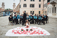 "VENICE, ITALY - 11 MAY 2017: Romina de Novellis' performance ""Inferno"", featuring 25 orchestra members, is seen here in Fondamenta Arsenale during the 57th International Art Exhibition in Venice, Italy, on May 11th 2017.<br /> <br /> The 57th International Art Exhibition, titled VIVA ARTE VIVA and curated by Christine Macel, is organized by La Biennale di Venezia chaired by Paolo Baratta. ""Viva Arte Viva is an exclamation, a passionate outcry for art and the state of the artist. Viva Arte Viva is a Biennale designed with artists, by artists and for artists, about the forms they propose, the questions they ask, the practices they develop and the ways of life they choose"", Christine Macel says. <br />  <br /> Rather than broaching a single theme, Viva Arte Viva offers a route that moulds the artists' works and a context that favours access and understanding, generating connections, resonances and thoughts. VIVA ARTE VIVA will unfold over the course of nine chapters or families of artists, beginning with two introductory realms in the Central Pavilion, followed by another seven across the Arsenale through the Giardino delle Vergini. 120 are the invited artists from 51 countries; 103 of these are participating for the first time. <br /> <br /> The Exhibition will also include 85 National Participations in the historic Pavilions at the Giardini, at the Arsenale and in the historic city centre of Venice. 3 countries will be participating for the first time: Antigua and Barbuda, Kiribati, Nigeria."