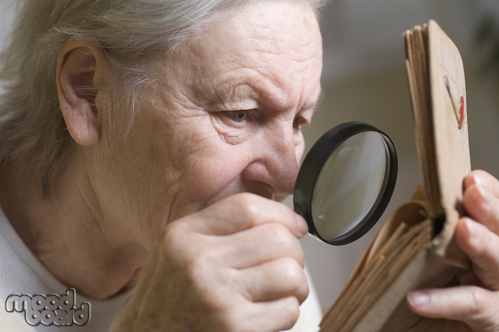 An old lady looking through a magnifying at a small photo book