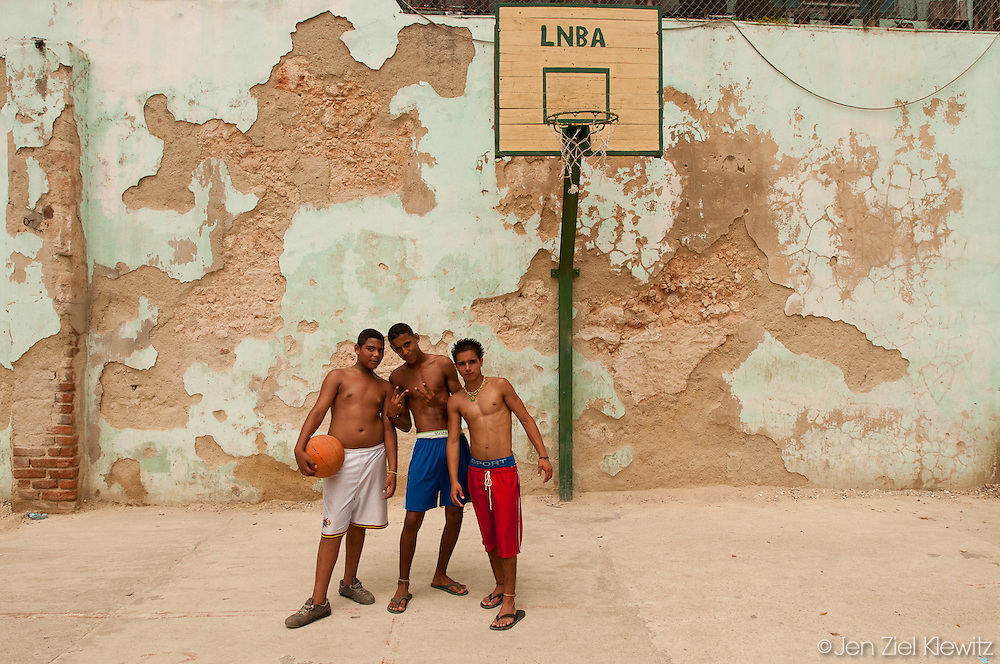 From left to right, Yaniel Mesa, 14, Yanel Boucer Forte, 15, and Vuriogoso Martinez, 14, pause for a portrait while shooting hoops at a community basketball court in Havana Vieja, Cuba.  Photo by Jen Klewitz