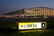 "An exterior view of Heathrow Airport's Terminal 5 building in West London. Created by the Richard Rogers Partnership (now Rogers Stirk Harbour and Partners). A lit airfield navigation taxiway sign shows the route number and code for pilots to find their way around the confusing network of taxiways and there are 1 million square metres of new apron and taxiway pavement for T5. At a cost of £4.3 billion, the 400m long T5 is the largest free-standing building in the UK with the capacity to serve around 30 million passengers a year. The Terminal 5 public inquiry was the longest in UK history, lasting four years from 1995 to 1999. From writer Alain de Botton's book project ""A Week at the Airport: A Heathrow Diary"" (2009). ..."