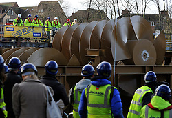 © Licensed to London News Pictures. 20/12/2011, Windsor, UK. Workers and members of the media watch the operation from the river bank. One of the two giant 40 tonne Archimedes screws is lifted into place at Romney Weir on the River Thames. The screws, the largest in the UK and fish friendly, will generate 300 kilowatts of energy every hour to power Windsor Castle. It is the largest hydropower scheme in the South East of England. Photo credit: Stephen Simpson/LNP