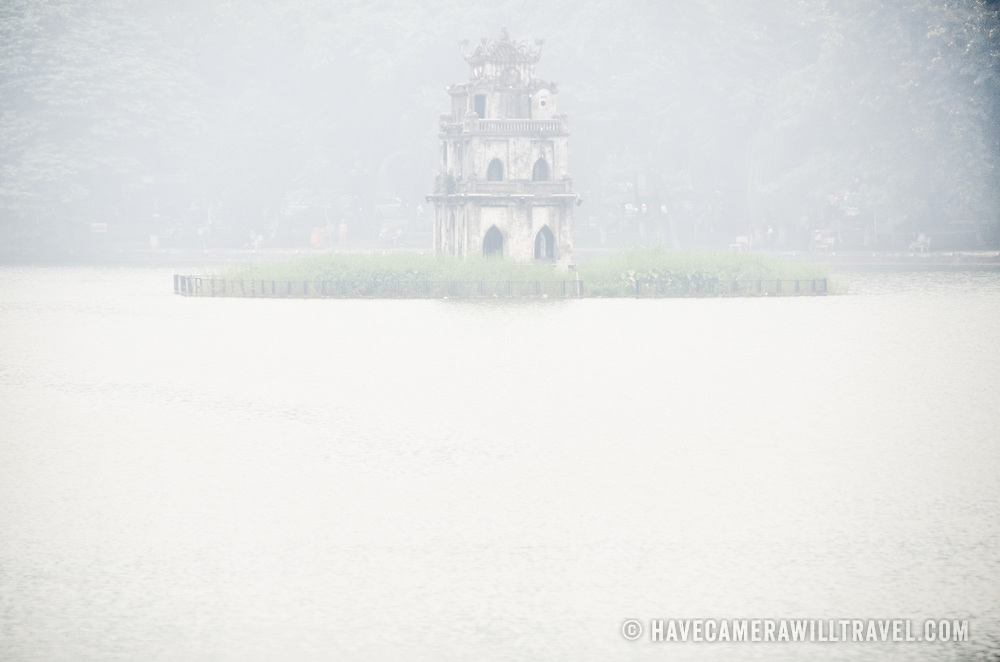 Turtle Tower (Thap Rua), on a small island in the middle of Hoan Kiem Lake in the heart of Hanoi is partially obscured by a thick morning fog. Copyspace on the water at bottom.