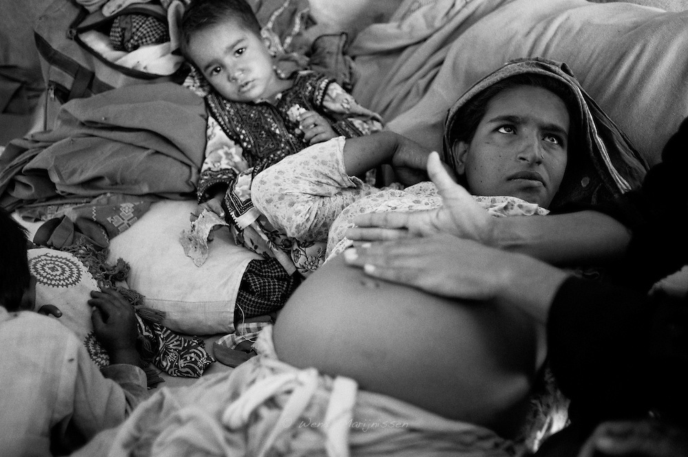 A midwife checks the position and growth of Hamida's baby. Nervously she looks at the midwife to find out if everything is alright. Karachi, Pakistan, 2010
