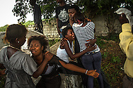 EL SEIBO, DOMINICAN REPUBLIC - OCTOBER 13, 2013: A sister and other family members mourn during the burial of a young woman born in the Dominican Republic, to Haitian parents, who was affected by judgment TC/0168, handed down by the Constitutional Court of the Dominican Republic.  The ruling essentially revokes Dominican citizenship from tens of thousands of people born in the Dominican Republic, which means they cannot have access to government services, id's necessary for legal work and travel, and the children cannot attend public school.  NGO workers said the day before she died, the woman had  been trying to get a birth certificate for her baby, which as denied.  The woman said he was very upset for not being able to register her baby, despite that it had been born in the Dominican Republic. Family members could not afford to pay for an autopsy, nor to prepare her body for burial, so they buried her the same day that she died.  Because of the judgement, family members could not get a death certificate. CREDIT: Meridith Kohut for The New York Times