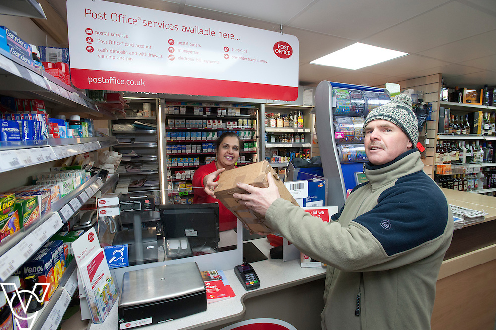 Pictured postmaster Kanchan Lakhman serving customer Ian Young<br /> <br /> Thringstone Post Office, 19-23 Loughborough Road, Thringstone, Leicestershire.<br /> Date: January 23, 2015