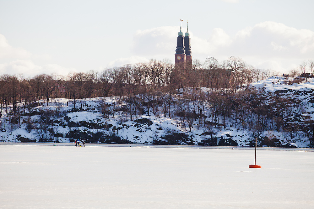 People fishing on the frozen lake M&auml;laren, Riddarfj&auml;rden, in Stockholm.  The photo is taken from Kungsholmen with the island S&ouml;dermalm in the background.  <br /> H&ouml;galid Church to the right.