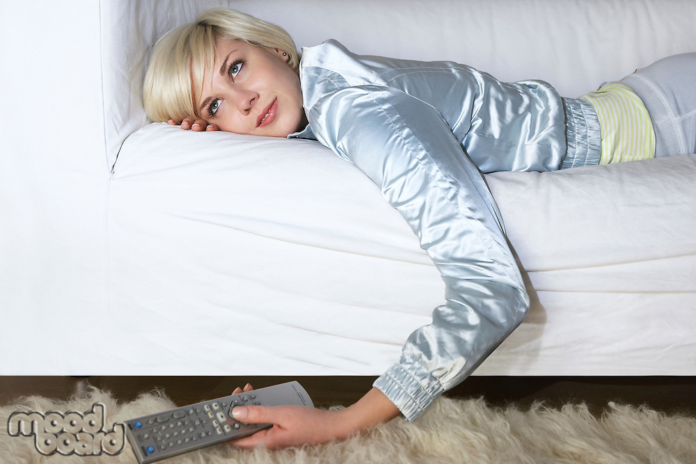 Woman lying on sofa holding remote control
