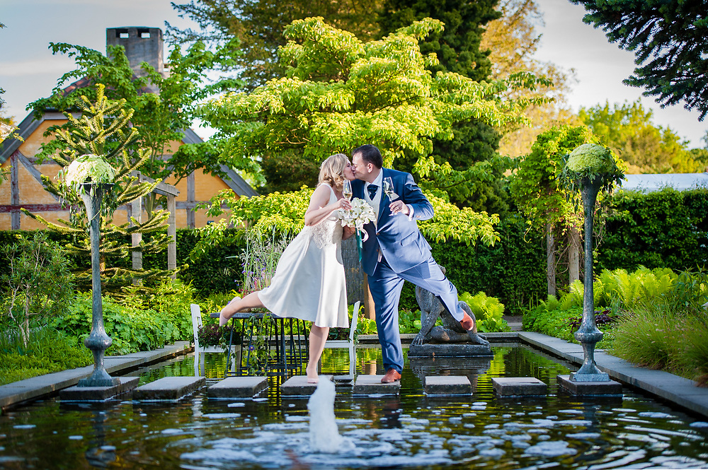 Newlyweds kissing atop a water feature.