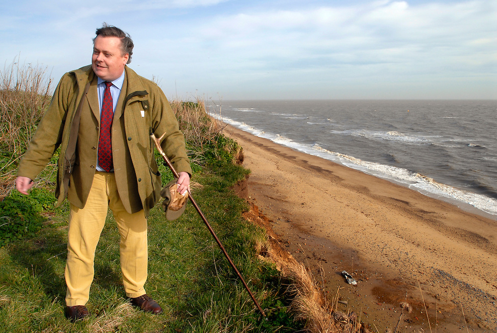 UK. Suffolk. Covehithe. Parts of this Suffolk coast line are disappearing at the rate of 6-12 meters a year due to coastal erosion. .Photos show Estate Manager for Benacre, Mark Benmore-Roland (yellow trousers) and tenant farmer Roger Middleditch (cap and dark jacket) viewing Roger's disappearing farmland..