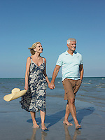 Senior couple walking on tropical beach