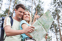 Happy young hiking couple holding map with woman pointing away in forest
