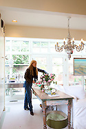 The Portland, Oregon home of Wendy Burden, author of  the memoir, Dead End Gene Pool.  Ms. Burden arranging camelias in her kitchen.