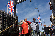 Seen from the steps of Westminster underground tube station, foreign tourists walk along Whitehall days before the royal wedding ceremony of Prince William and Kate Middleton. Their spending and interest in this state occasion will bring in millions of Pounds into the country's exchequer, bolstering local businesses at a time of debt and recession. The Union Jack flies along the wedding procession route as the nation prepares to celebrate the state occasion.