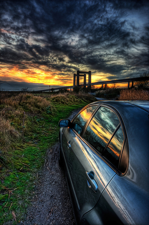Evening sunset over the river swale reflected in the side of a shiny car with the new and old swale bridges on the horizon