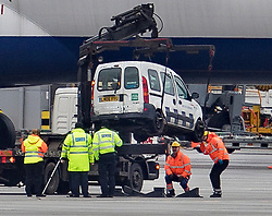 © Licensed to London News Pictures. 14/02/2018. London, UK. Police inspect the underside of a damaged British Airways vehicle as they lift it from the tarmac at Heathrow Airport after this morning's fatal crash near Terminal 5. Photo credit: Peter Macdiarmid/LNP