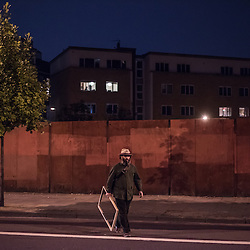 London, UK - 11 September 2014: A man holding a wooden frame crosses Kingsland Road in Dalston, North-East London.