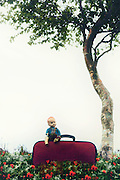an old doll is sitting on a red suitcase