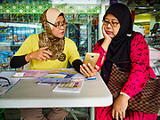 13 DECEMBER 2018 - SINGAPORE: A life skills instructor (yellow tee shirt) helps adults with their smart phone in the Geylang neighborhood. The government of Singapore subsidizes life skill classes to help people cope with new technology, including classes for smart phones and tablets tailored to older adults. The Geylang area of Singapore, between the Central Business District and Changi Airport, was originally coconut plantations and Malay villages. During Singapore's boom the coconut plantations and other farms were pushed out and now the area is a working class community of Malay, Indian and Chinese people. In the 2000s, developers started gentrifying Geylang and new housing estate developments were built.    PHOTO BY JACK KURTZ