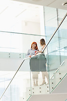Businesswomen having coffee while standing on steps in office