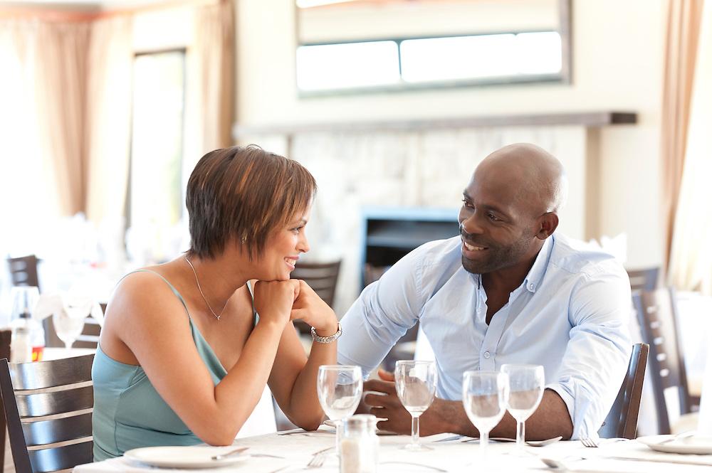 Couple relaxing chatting an=d flirting at restaurant dinner table.