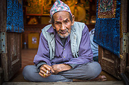 An old Thangka painter from Bhaktapur, Nepal, is  smocking a cigarette on the entry of his shop. The hat on his head is called &quot;Dhaka Topi&quot; and is usually given away as gifts during Dashain and Tihar festivals. <br />