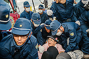 Protestors outside the main gate of Camp Schwab. Many of the protestors are elderly people who try to block the entrance using their bodies. Large groups of police come out in force when vehicles carrying building material are about to enter the US Military Base. Each protestor is often removed by several policeman carrying the individual away from the entrance. Henoko, Okinawa, Japan.