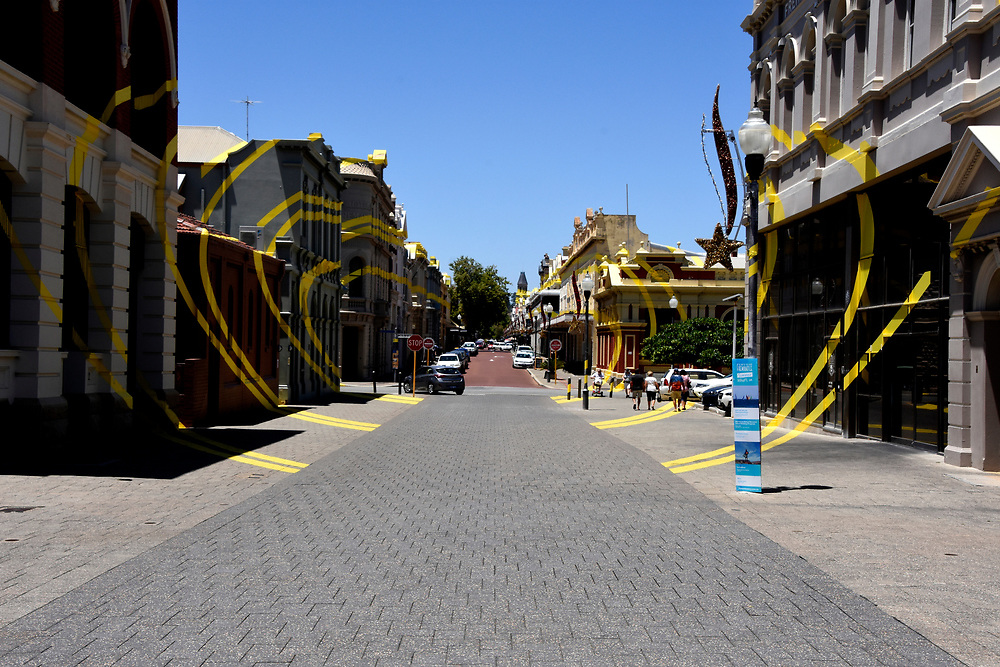 A street in Freemantle with yellow lines on the pavements and buildings