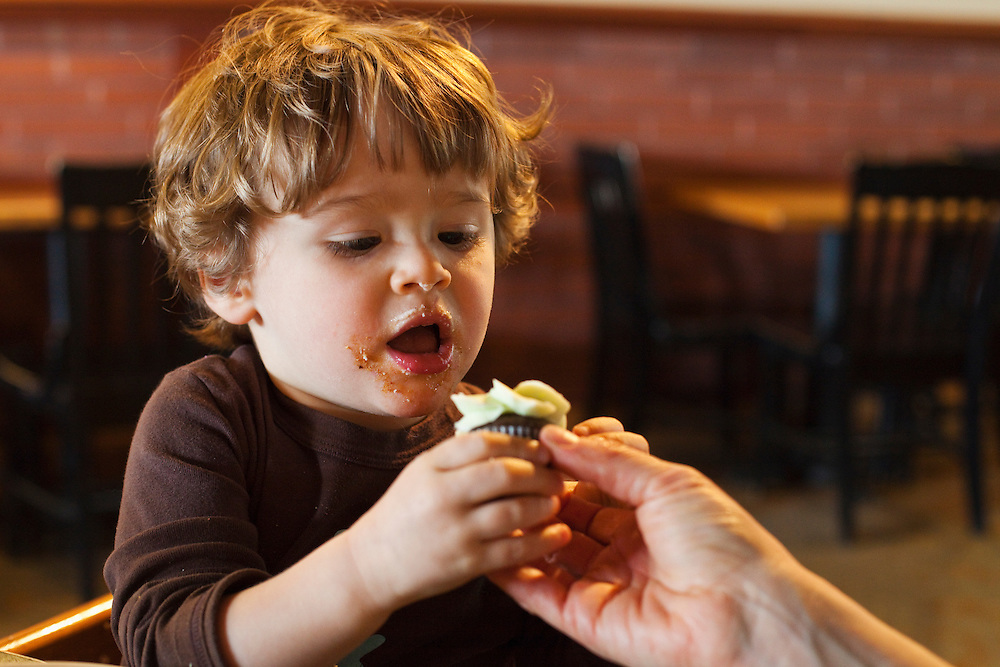 A toddler with a messy face taking a cupcake from his mothers hands.