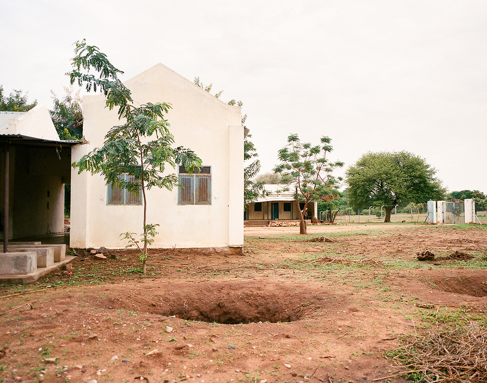 "NUBA MOUNTAINS, SUDAN – JUNE 9, 2018: A foxhole can be seen on the property of the former State Hospital in Kouda, where four parachute bombs were dropped in 2014. Miraculously, none of the ordinances exploded, and can still be seen protruding from the ground surrounding the hospital compound.<br /> <br /> In 2011, the government of Sudan expelled all humanitarian groups from the country's Nuba Mountains. Since then, the Antonov aircraft has terrorized the Nuba people, dropping more than 4,080 bombs on hospitals, schools, marketplaces and churches. Today, vestiges of the Antonov riddle the landscapes of daily life, where more than 1 million Nuba live in famine conditions – quietly enduring the humanitarian blockade intended to drive them out of the region. The skies are mostly clear. Yet the collective memory of the bombings remains an open wound, and the Antonov itself a persistent threat. So frequent were the attacks that the Nuba nicknamed the high flying aircraft and its dismal hum: ""Gafal-nia ja,"" they would declare, running to the hillsides. ""The loss of appetite has come."""