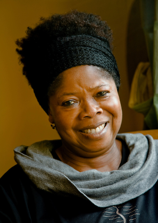 Head and shoulders portrait of a black woman seated in front of a window and smiling at the camera.