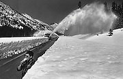 As a pair of snowplows carves out the North Cascades Highway near Washington Pass, a Highway District 2 supervisor sucks on a favorite local refreshment, of which there seems an unlimited supply - the original snow cone. (Tom Reese / The Seattle Times, 1988)