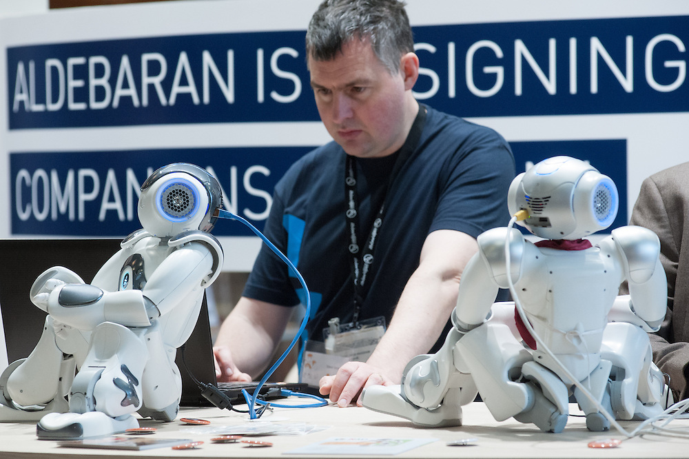 Lyon, France - 19 March 2014: an Aldebaran engineer works with NAO Robots  at Innorobo 2014, the 4th international trade show on service robotics.