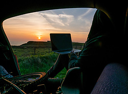 Man Sitting in Car Boot at Sunset Using Laptop Computer