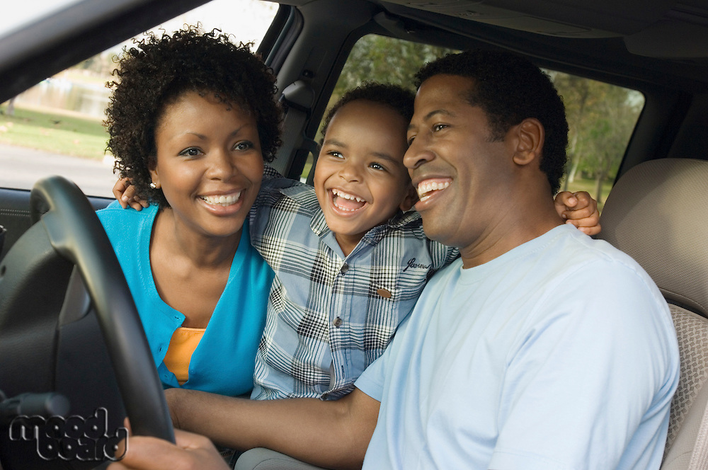 Family smiling together on driver's seat close-up