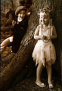 Jessica and Louis Focht play dress ups under a giant tree in the pacific northwest.