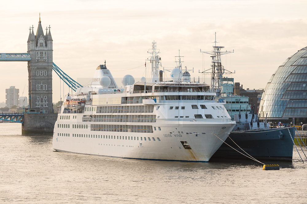 © Licensed to London News Pictures. 01/08/2017. LONDON, UK.  Silver Wind, a huge 514 feet long, 17,400 ton cruise liner seen moored next to HMS Belfast before she leaves London under Tower Bridge this morning after a brief visit, towed backwards by two tugs. Silver Wind carries just 296 passengers and its owner, Silversea claim that the ship has amongst the highest space-to-guest ratios in the cruise ship industry, with the largest suites measuring 1,314 square feet. Tickets cost thousands of pounds, but all guest expenses, even champagne are included in the price. Environmentalists claim the pollution created by giant cruise ships outweigh their economic benefits. The Port of London Authority (PLA) are conducting a work programme during 2017 to monitor air quality and pollution caused by river traffic on the River Thames.  Photo credit: Vickie Flores/LNP