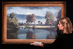 "© Licensed to London News Pictures. 12/11/2018. London, UK. A staff member hangs ""The Stour, near Sudbury"" by Algernon Cecil Newton (1880- 1968) oil on canvas (Estimate £40,000-60,000).<br /> Bonhams Modern British and Irish Art photocall. Auction to be held on 14 November 2018. Photo credit: Dinendra Haria/LNP"