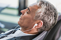 Portrait of mature businessman listening to music on his smartphone while sleeping and waiting for boarding in airport